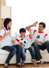 Joyful family watching football match