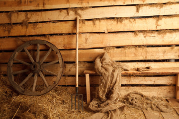 Interior of village building: wheel, pitchfork, bench...