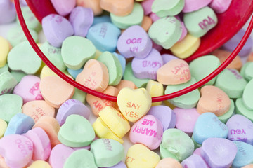 Heart shaped candy spilling from a red bucket.