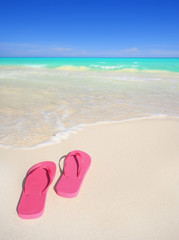 A pair of pink sandals on a white sand beach