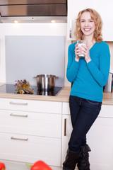 junge frau mit milchglas in küche
