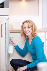junge frau nimmt milchflasche aus dem kühlschrank