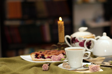cup of tea against a background of burning candle, pie, flowers