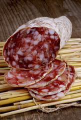 Sliced salami on a straw mat