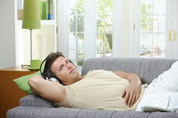 Man on sofa listening to music smiling