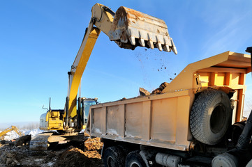 loader excavator loading earth to body of rear-end tipper