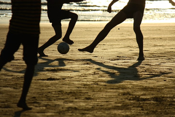 football game on the beach  agains the sun