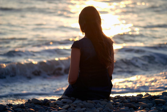 Silhouette of the girl sitting at seashore at sunset