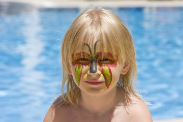 Girl with paint on his face in the pool