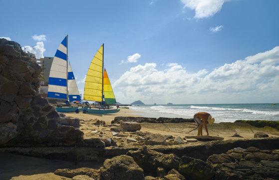Mazatlan, mexico. Man picking up sea shells.