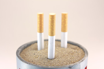 cigarettes in ashtray with sand