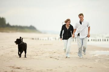 boy and girl runnig dog on the beach