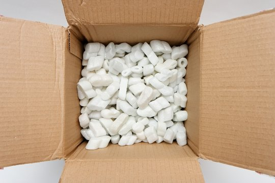 A cardboard box with packing foam pellets top view..