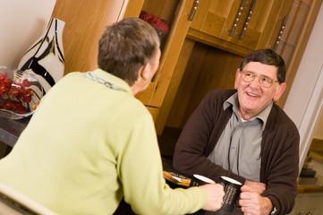 Senior man and woman talking in kitchen