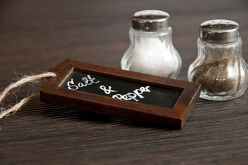 Salt and pepper shaker with chalkboard on wood