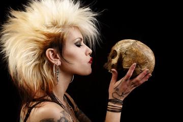 A sexy punk rocker woman holding a human skull.