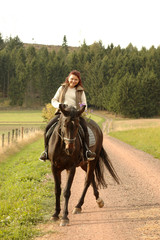 Horsewoman on tittup horse on country roads.