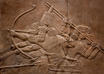 Ancient relief of assyrian warriors fighting in the war