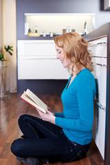 junge frau liest ein buch auf dem küchenboden