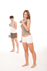 Fitness - Young couple training lifting weights on white