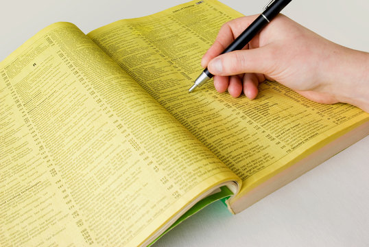 Search yellow pages with hand and pen