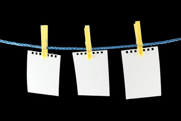 Blank pieces of paper hang on clothesline isolated on black