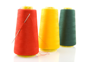 Three bobbins with threads and needle