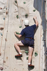 Man Climbing Rock Wall with Ropes