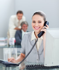 Charismatic businesswoman on phone working at a computer