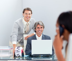 Smiling businessmen working at a computer together