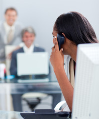 Afro-american businesswoman on phone at her desk