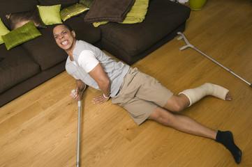 Homme plâtré avec des béquilles tombant au sol