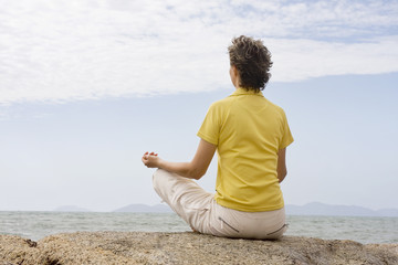 Frau meditiert am Meer