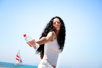 Beautiful young woman holding a bottle of water.