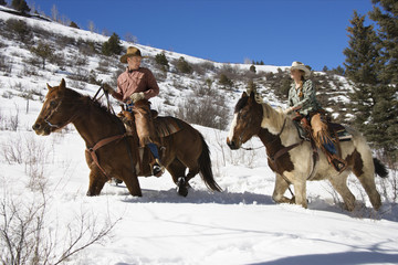 Man and Woman Riding Horses in the Snow