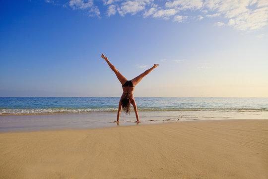 young woman doing a cartwheel on a hawaii beach