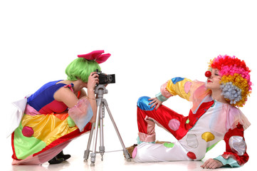 Two clown-girls in wigs and fancy costumes taking photos