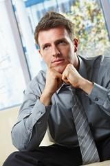 Portrait of sitting businessman thinking