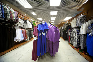 Dresses, blouses, jackets and suits in shop of female clothes