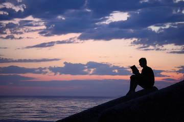 Silhouette guy sitting on breakwater in evening near sea, reads