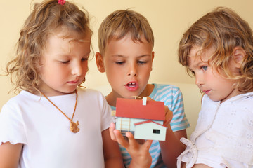 children three together keeping in hands model of house
