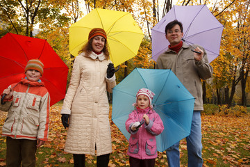 Family from four persons in autumn park with umbrellas.