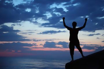 Silhouette guy lifted hands upwards on breakwater in evening