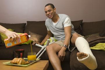Homme platré se faisant servir un jus d'orange