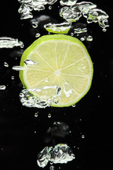 Lime (lemon)  falling in water on black