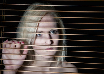 Beautiful young blonde woman trapped behind blinds