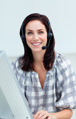 Confident businesswoman with headset on working at a computer