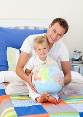 Smiling father and his son looking at a terretrial globe
