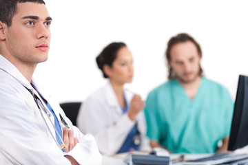 Young doctor thinking deeply, collegues discussing behind