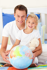 Attentive father and his daugther looking at a terrestrial globe